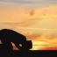 Mensch beim Gebet im Sonnenuntergang